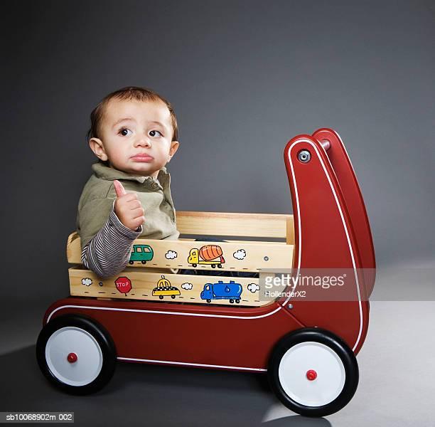 Baby boy (6-11 months) sitting in toy wagon, studio shot