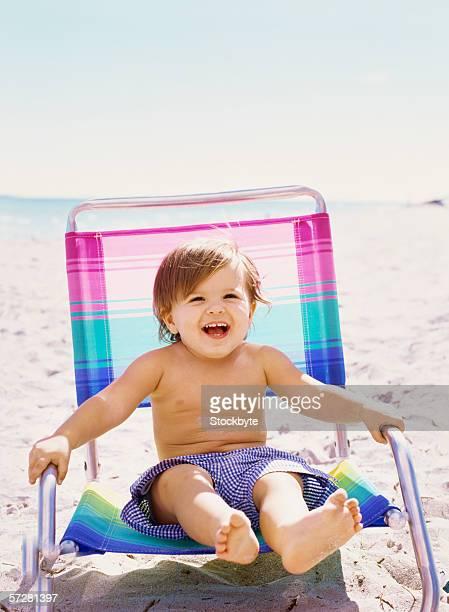 Baby boy sitting on a deck chair on the beach