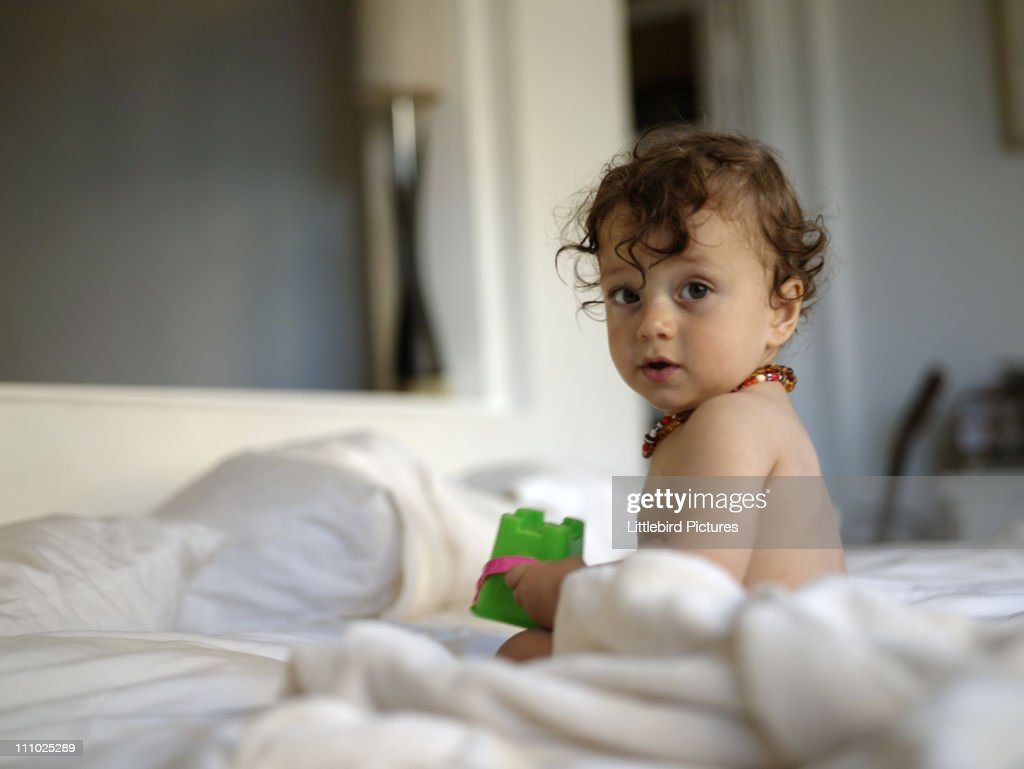 baby boy sitting on bed : Stock Photo