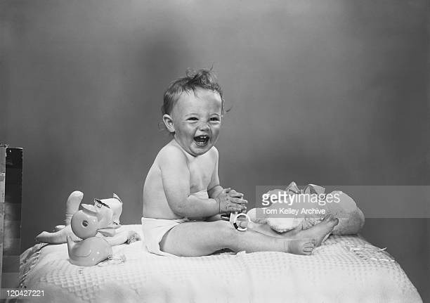 Baby boy sitting on bed with toys, laughing