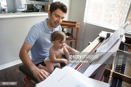 Baby boy sitting on fathers knee playing piano