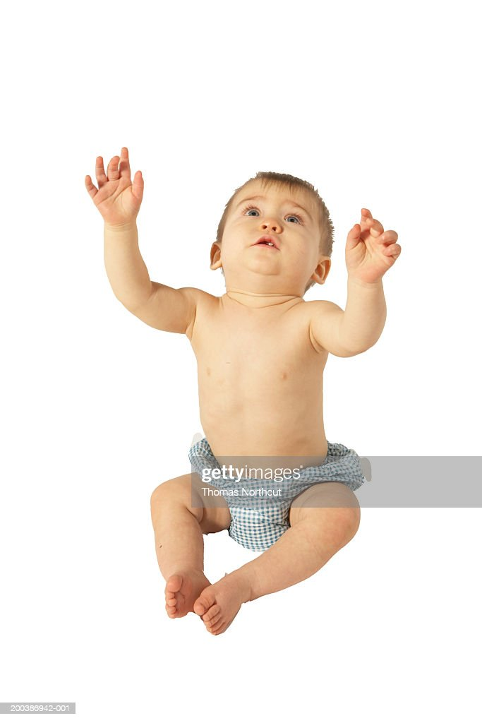 Baby boy (9-12 months) sitting on floor, looking up, arms raised : Stock Photo