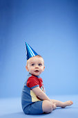 Baby boy (9-12 months) sitting on floor wearing party hat