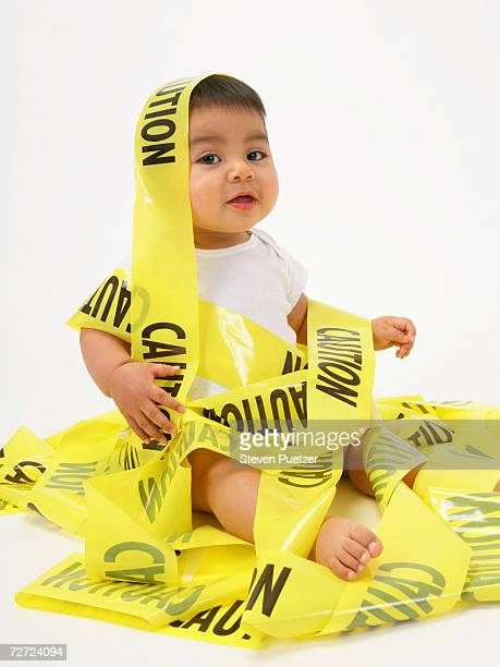 Baby boy (15-18 months) sitting on floor wrapped in 'caution' tape