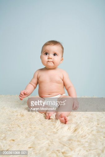 Baby boy (4-7 months) sitting on rug, looking up : Stock Photo