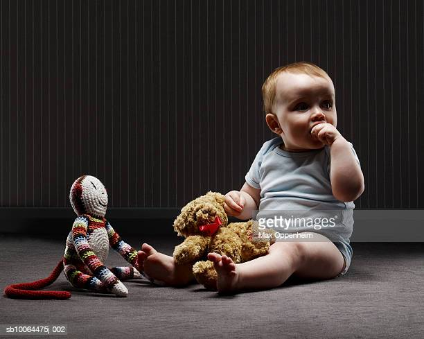 Baby boy (9-12 months) sitting with soft toys on floor