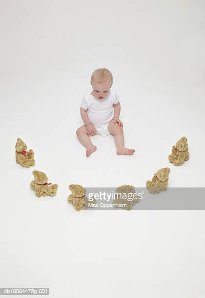 Baby boy (6-9 months) sitting with teddy bears on floor, elevated view