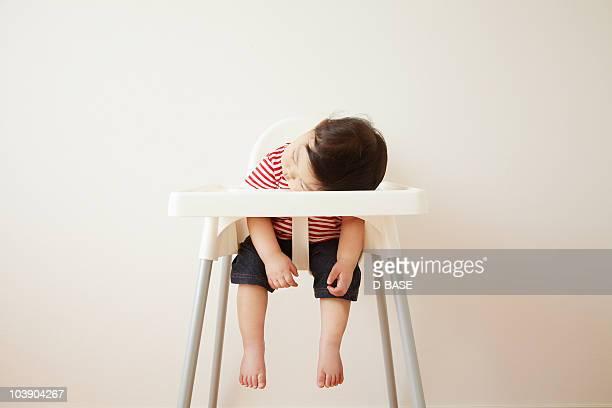 A baby boy sleeping in a high chair