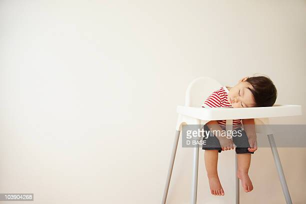 A baby boy sleeping in a high chair