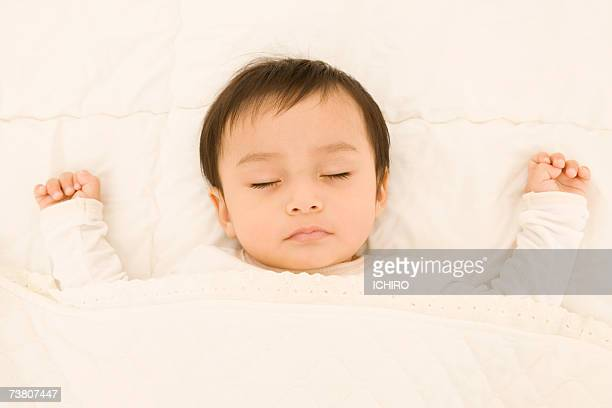 Baby boy (9-12 months) sleeping, wearing santa hat