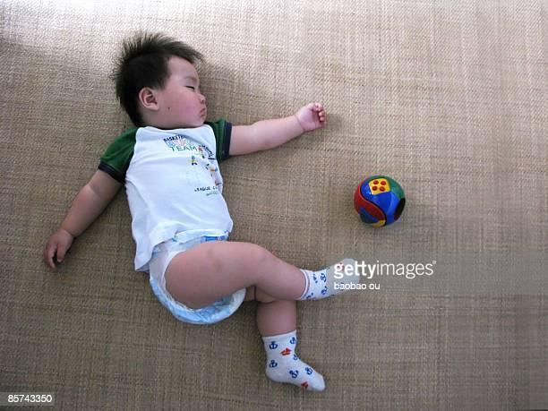 Baby boy sleeping with football beside