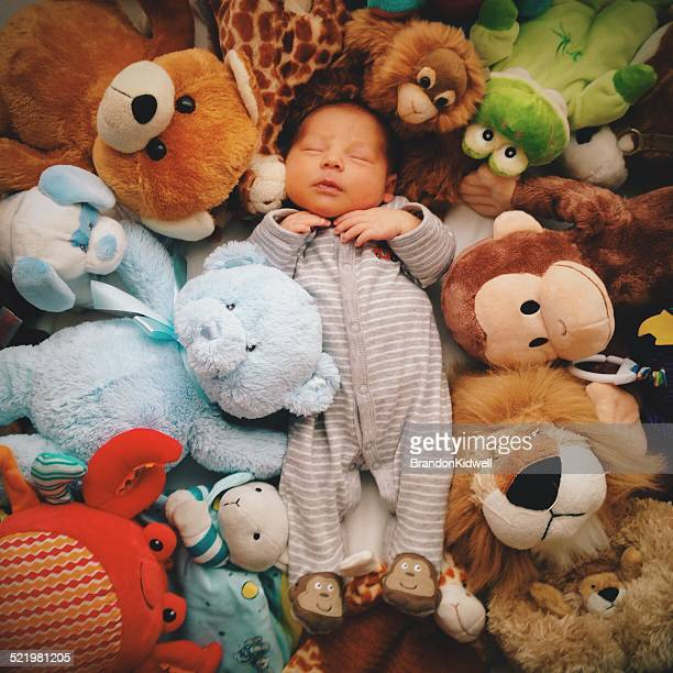 Baby boy sleeping with soft toys