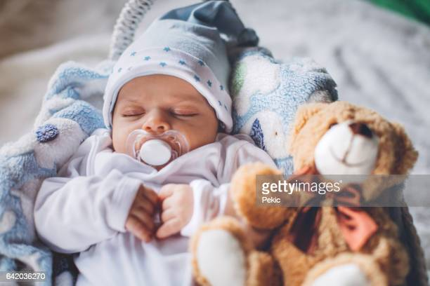 Baby boy sleeping with teddy bear and pacifier