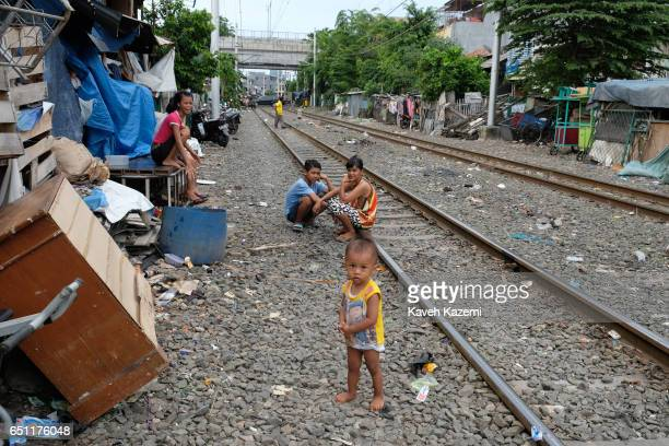 A baby boy slum dweller with no shoes stands outside his parents hut by the rairoad track in Kota City on November 25 2016 in Jakarta Indonesia The...