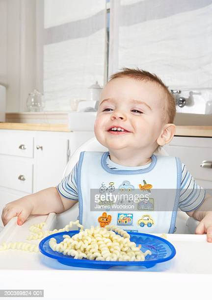 Baby boy (9-12 months) smiling in high chair, close-up