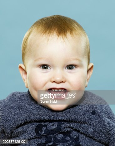 Baby boy (9-12 months) smiling, portrait, close-up : Stock Photo
