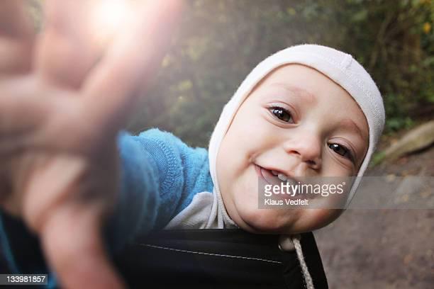 Baby boy smiling reaching for camera
