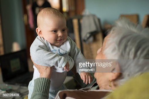 Baby boy smiling to an elderly woman at home