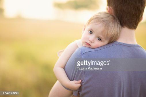 Baby boy snuggling against his father : Stock Photo