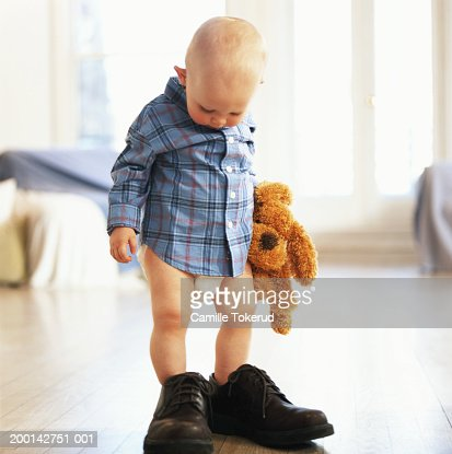 Baby boy (9-12 months) standing in adult's shoes, holding stuffed toy