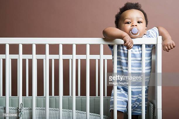 Babymode – Jungen stehen in Kinderbett