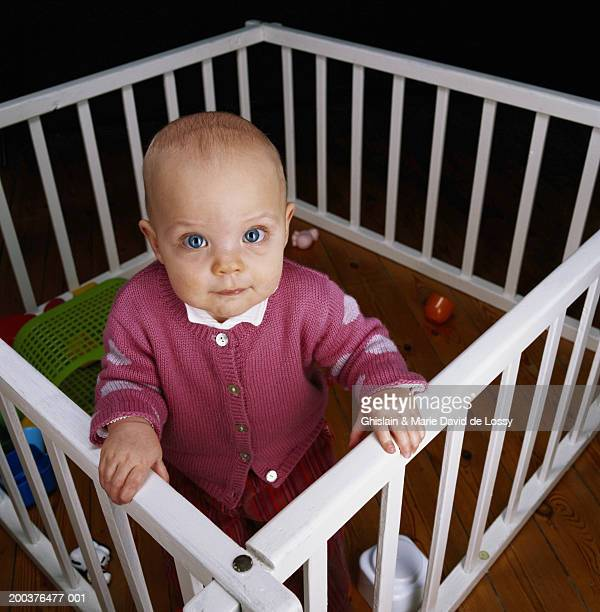 Baby boy (9-12 months) standing in crib, elevated view, portrait