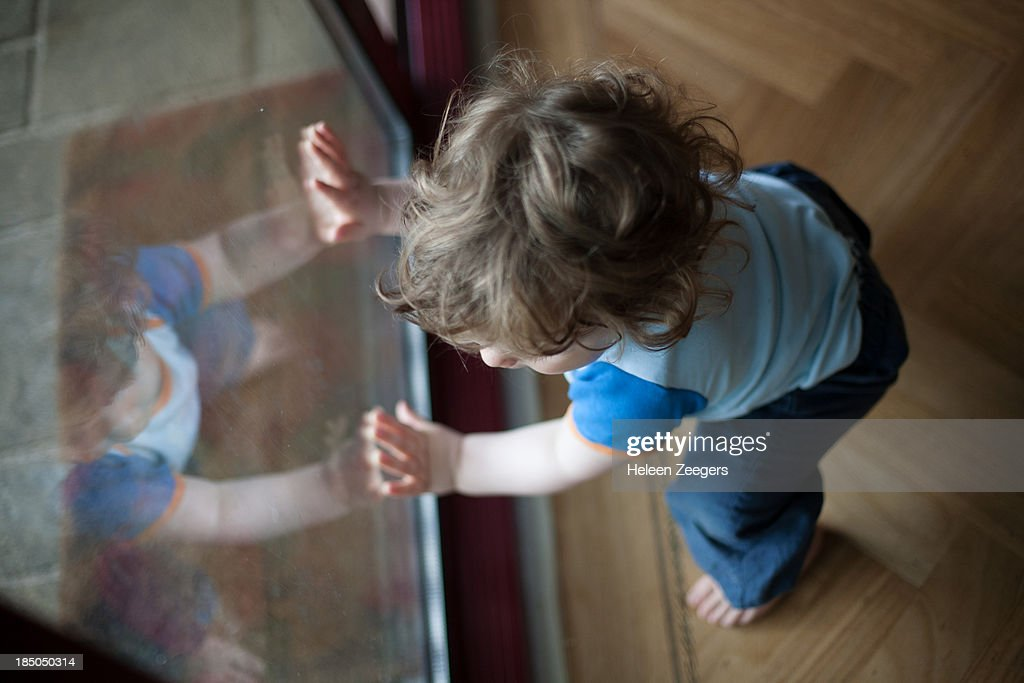 baby boy standing up holding on to window : Stock Photo