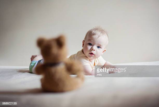 Baby boy staring at toy bear