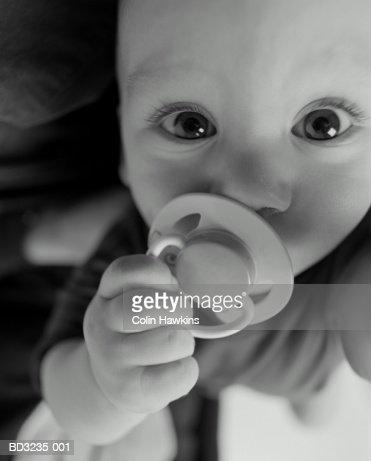 Baby boy (3-6 months) sucking dummy, close-up (B&W) : Stock Photo