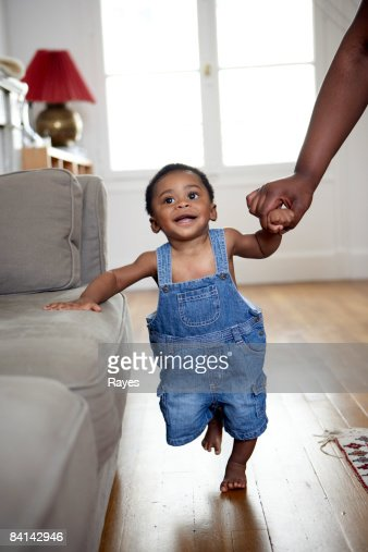 baby boy taking first steps holding mothers hand