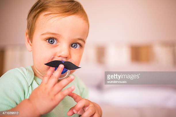 Baby boy touching a moustache that's stuck onto his pacifier
