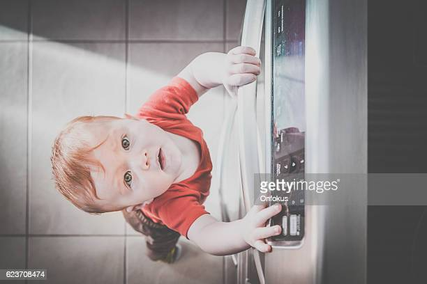 Baby Boy Touching Grabbing Oven Handle in Kitchen