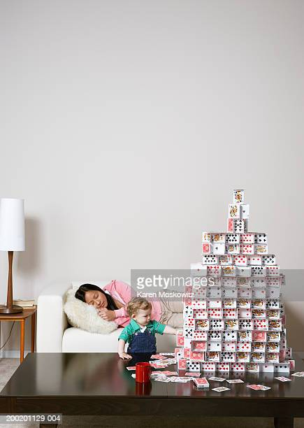 Baby boy (9-12 months) touching house of cards, woman sleeping on sofa
