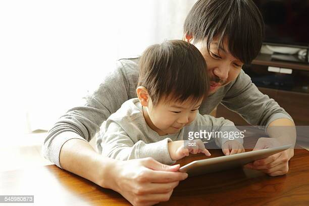 Baby boy using digital tablet with father