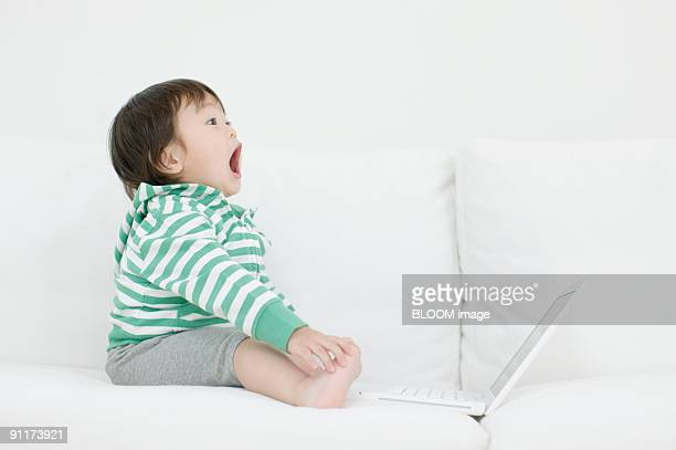 Baby boy using laptop on couch, with surprised expression