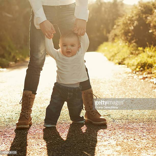 Baby boy walking with mother