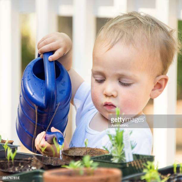 Baby boy watering the plants