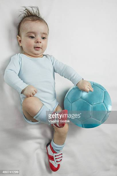 A baby boy wearing baby soccer shoes kicking towards a soccer ball