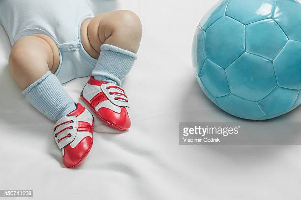 A baby boy wearing baby soccer shoes lying next to a soccer ball