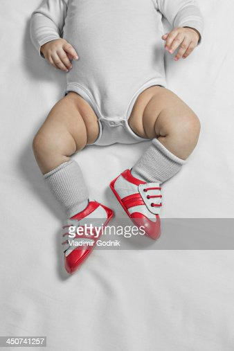 A baby boy wearing baby soccer shoes, waist down