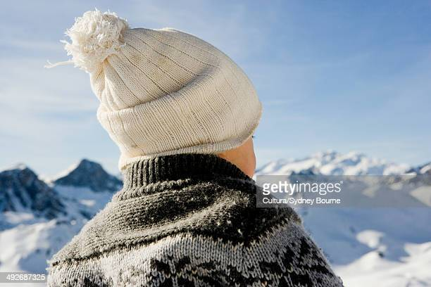 Baby boy wearing knitted bobble hat, mountain scenery in background