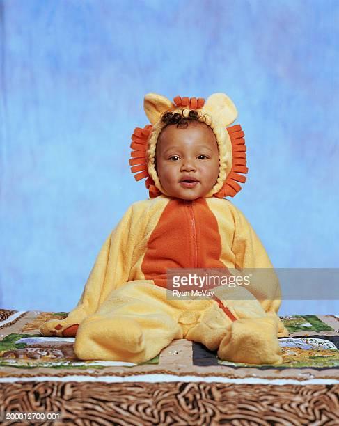 Baby boy (12-15 months) wearing lion costume, portrait