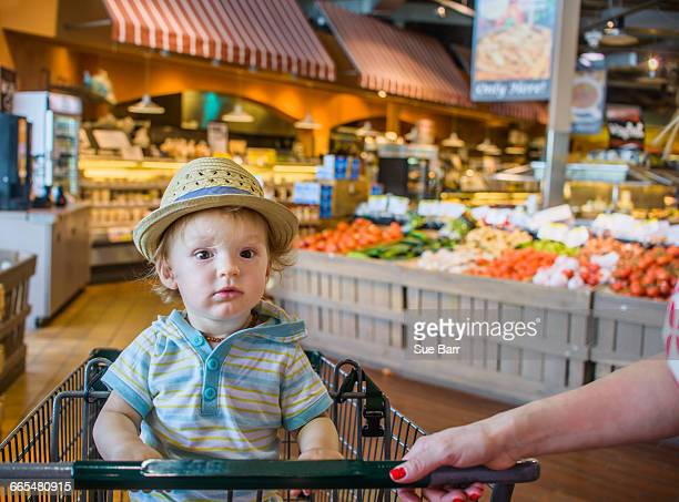 Baby boy wearing straw hat sitting in shopping trolley