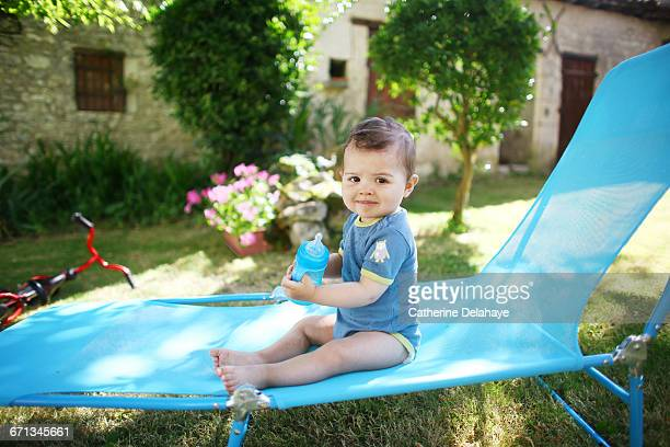 A baby boy with a goblet on a deck chair
