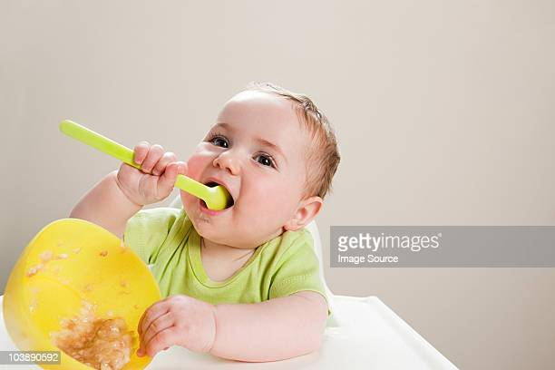 Baby boy with bowl of babyfood