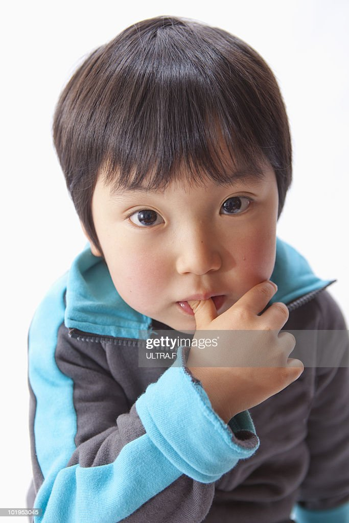 Baby boy with finger in mouth : Stock Photo