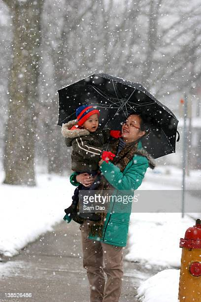 Baby boy with his mom in snowfall