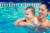 Cute baby boy enjoying with his mother in the pool.