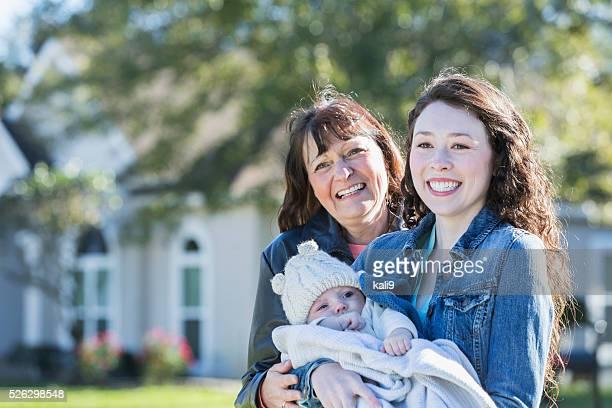 Baby-Junge mit Mutter und Großmutter außerhalb Haus