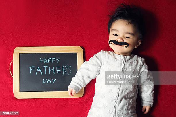 Baby boy with moustache greets Happy Father's Day